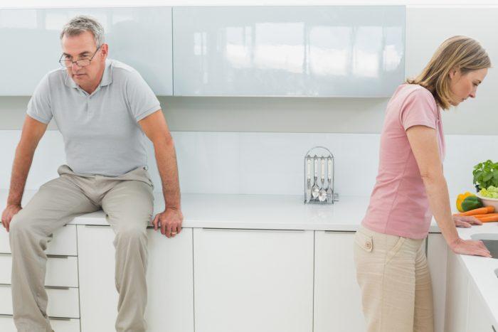 Ein Mann sitzt auf Küche und die Frau lehnt sich auf die Küche.