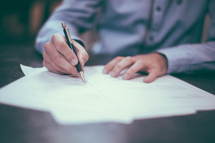 Ein Mann unterzeichnet einen Arbeitsvertrag