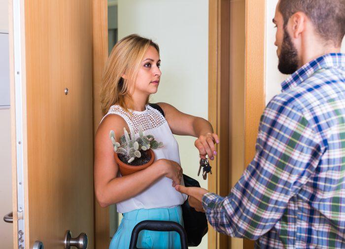 Frau mit Kaktus im Arm gibt Mann einen Schlüssel