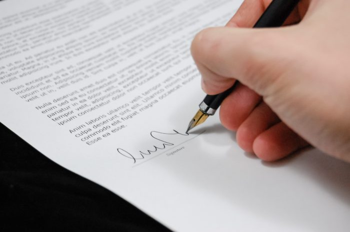 Mann unterzeichnet Vertragsformular für eine Mietwohnung.