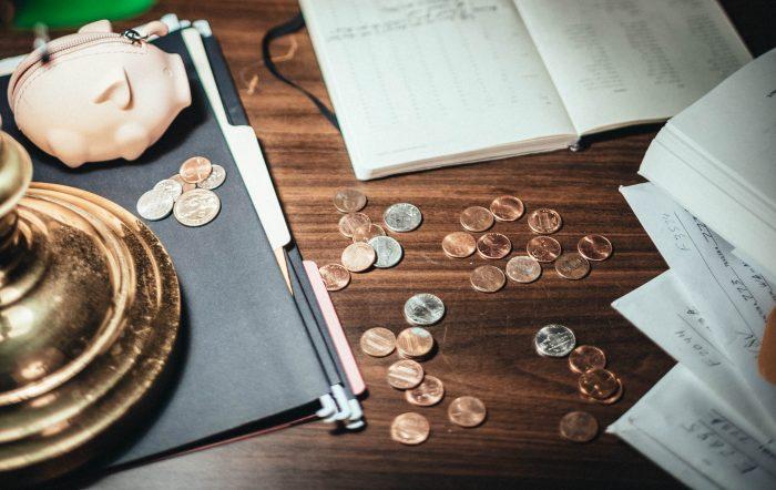 Auf einem Tisch liegen Münzen, Rechnungen und ein Sparschwein.