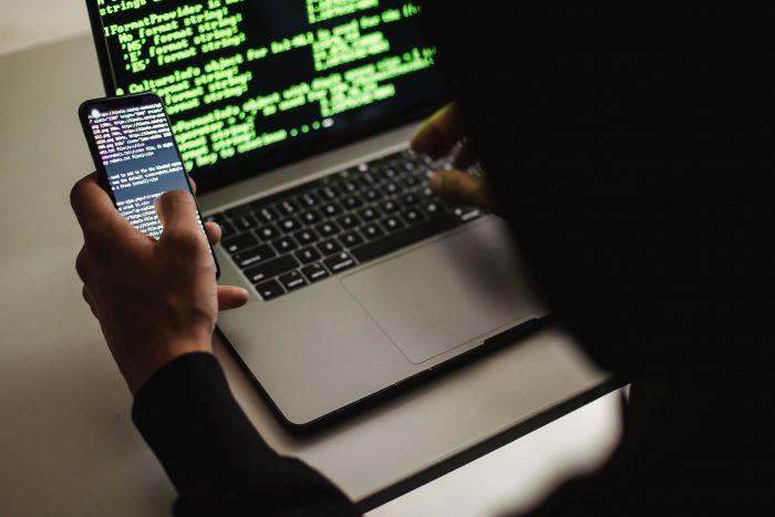 Eine Person sitzt am Laptop und hält ein Handy in der Hand.