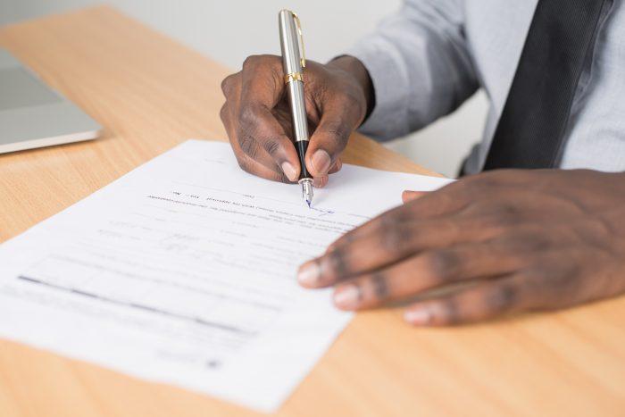 Mann unterzeichnet Vertrag.