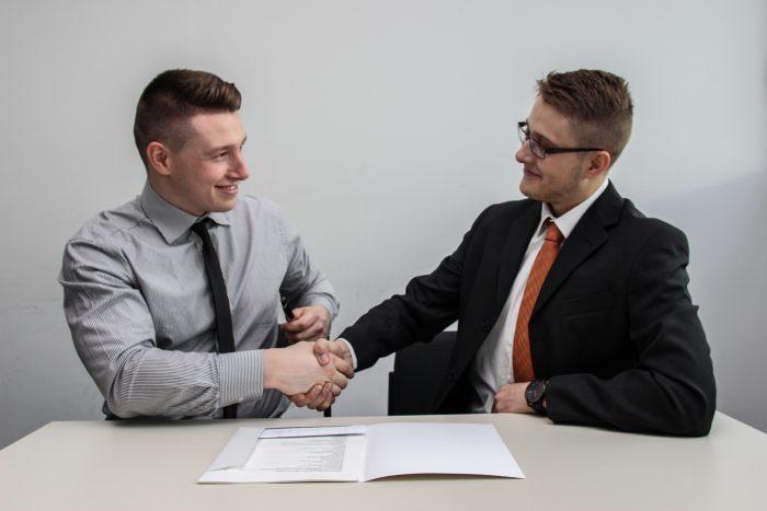 Zwei Männer im Anzug, die einander die Hand geben.